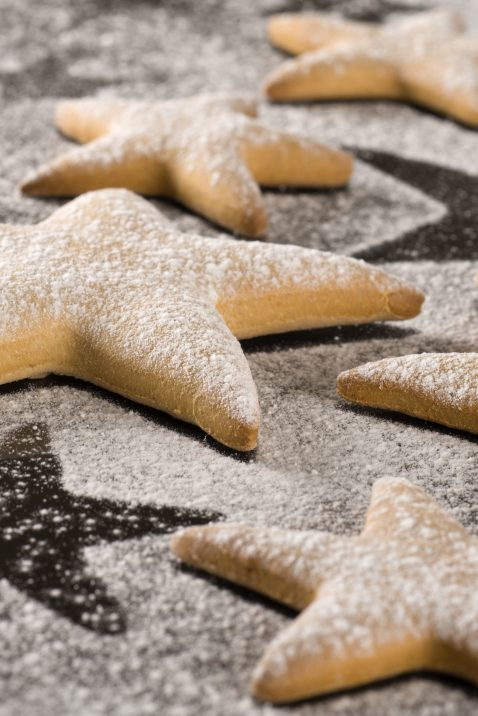 """Close up of star shaped cookies, dusted with fine sugar."""